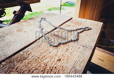 Chainsaw Chain Laying On A Scaffold Plank On Construction Site.