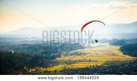 Two paragliders are flying in the valley. Paragliding from the mountain with perfect view