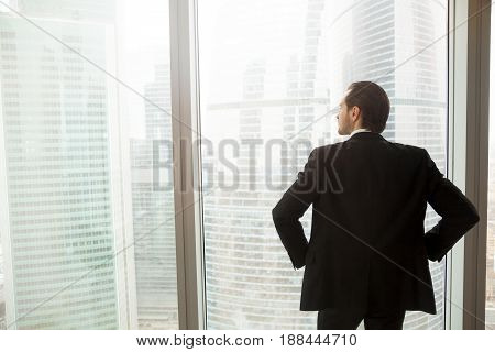 Back view of man in suit standing with hands on hips looking on cityscape outside the window. Successful businessman thinking about future plans, guy dreams about great career. Ambitions in business