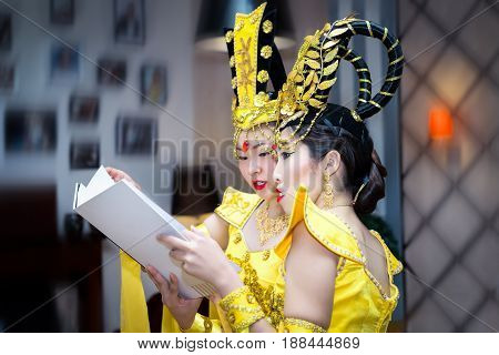 two asian actress in a yellow traditional chinese stage costume reading booklet