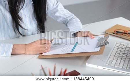 Business woman sitting at the table and wrote the paper