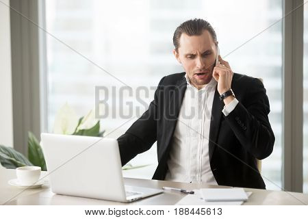 Angry businessman talking on the cellphone at work desk in office. Stressed entrepreneur arguing on the phone, unpleasantly surprised with bad news, hearing about unexpected problems in business