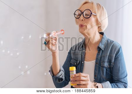 Great day. Joyful woman putting lips in roll looking attentively at her hand while blowing on stick with soap