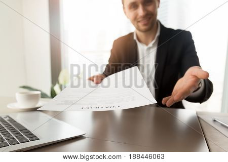 Company lawyer or representative offers to read and sign a contract. Smiling guy at desk reaching out contract to a partner. Successful entrepreneur promising good deal with beneficial terms. Close up