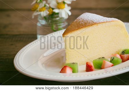 Homemade Japanese cheesecake. Delicious soft cheesecake fluffy,lite and soft.  Japanese cotton cheesecake serve with sparkling icing fresh fruit : kiwi and strawberry.  Japanese cheesecake on white plate put on rustic wood table for your relax time. Low f