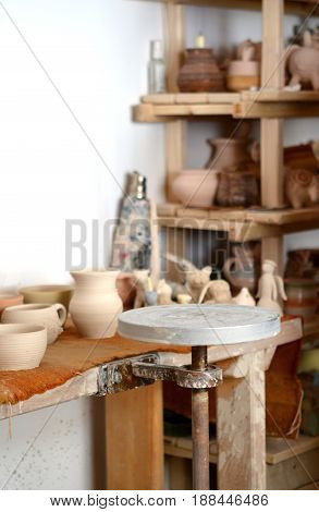 pottery manufactory, empty potter's wheel, pottery from clay on the table