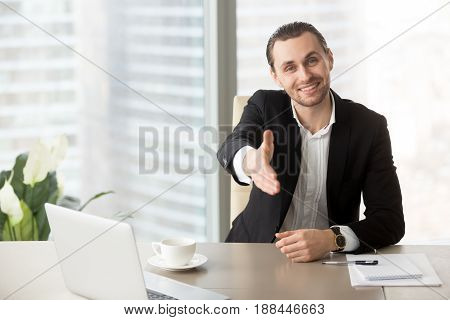Smiling young entrepreneur expert offers handshake at office desk. Positive businessman welcomes business partners on negotiations. Happy manager glad to see colleagues on meeting, satisfied with deal