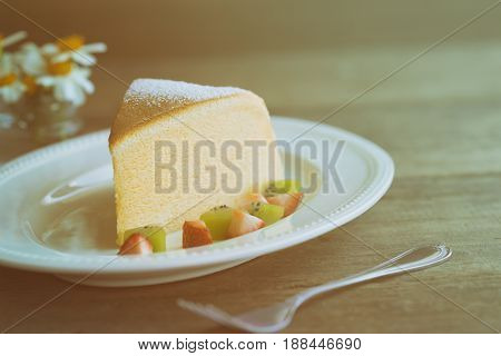 Homemade Japanese cheesecake. Delicious soft cheesecake fluffy,lite and soft. Japanese cotton cheesecake serve with sparkling icing fresh fruit : kiwi and strawberry.  Japanese cheesecake on white plate put on rustic wood table for your relax time. Low fa