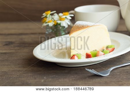 Homemade Japanese cheesecake. Delicious soft cheesecake fluffy,lite and soft. Japanese cotton cheesecake serve with sparkling icing fresh fruit : kiwi and strawberry. Japanese cheesecake on white plate put on rustic wood table for your relax time. Low fat