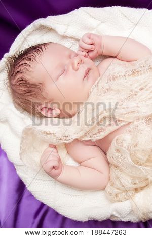 Newborn baby sleeping wrapped in a light cloth, child