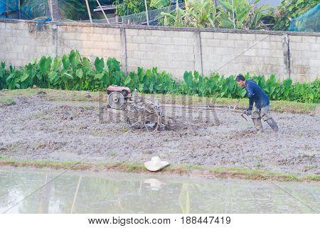 CHIANG RAI THAILAND - MAY 25 : unidentified Thai farmer plowman using tiller tractor pushcart in rice field on May 25 2017 in Chiang rai Thailand.