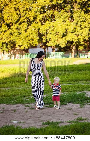 Baby boy walking in the park with mom's support, child