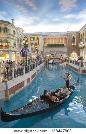 VENETIAN MACAU CHINA - AUGUST 22 2014 : tourist in gondola boat scene in venetian hotel most popular traveling destination