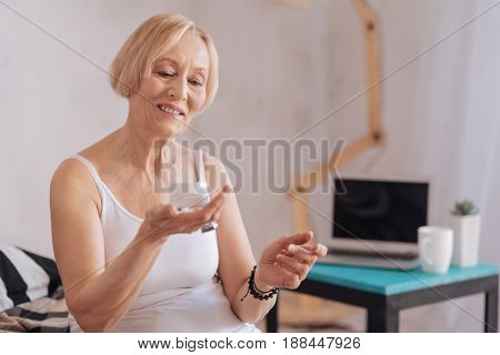 Test it. Attractive mature female holding jar with cream keeping smile on face while looking at her hand