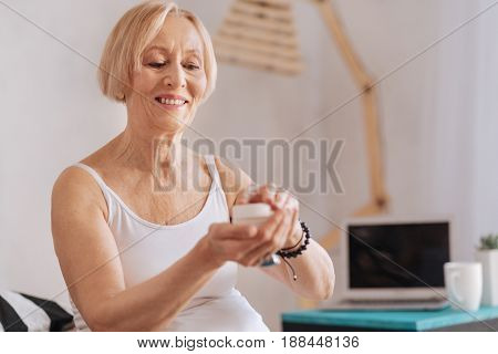 Open it. Delighted senior female holding arms bent in elbows keeping smile on her face while being in good mood