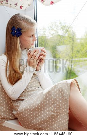 Beautiful child drinking tea and looking through window while sitting at windowsill at home