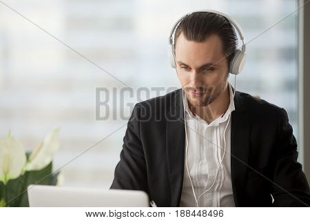 Young man in headphones listening music while working on laptop in office, watching video, live stream, webinar, enjoys web content. Entrepreneur takes part in online meeting or business negotiations