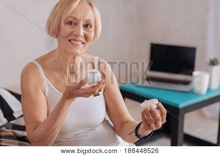 Nice smell. Positive delighted mature female keeping smile on her face holding bottle with care cosmetics while looking straight at camera