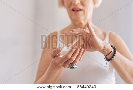 Try it. Close up of retired woman that holding jar with cream in right hand keeping mouth opened while testing it