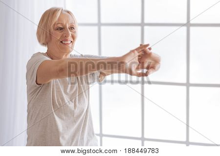 Morning exercises. Delighted female person stretching her arms looking forward while keeping smile on face