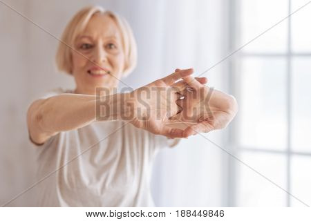 Follow me. Good-looking woman keeping smile on face joining fingers while looking forward