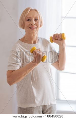 Great example. Positive delighted female retirement lifting dumbbells looking forward while standing in light room