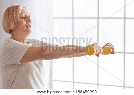 Concentrate on it. Healthy elderly female looking forward keeping arms with dumbbells in the air while standing in semi position