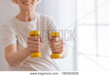 Control everything. Positive delighted woman keeping smile on her face holding sport equipment in both hands while doing exercises