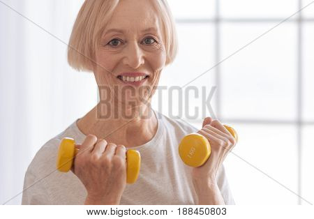 Watch me. Good looking female person looking straight at camera and holding dumbbells in both hands while standing on the foreground