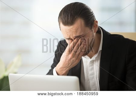 Frustrated businessman feels pain in eyes because of eyesight overstrain after long computer work. Tired young man massaging eyes in front of laptop. Eyes fatigue, headache or dizziness at workplace