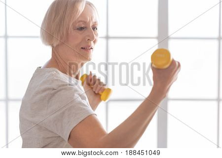 Just do it. Strong female wrinkling her forehead keeping mouth opened while looking at yellow dumbbells
