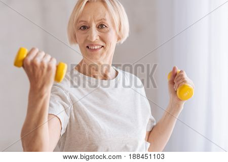 Ready to demonstrate. Attractive woman posing on camera with dumbbells in hands while expressing positivity