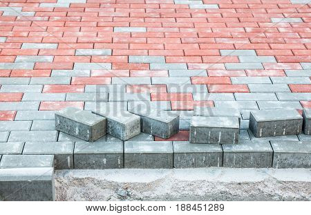 Paving the footpath with gray and red tiled cubes. Concrete border (curb-stone) at the edge of the path.