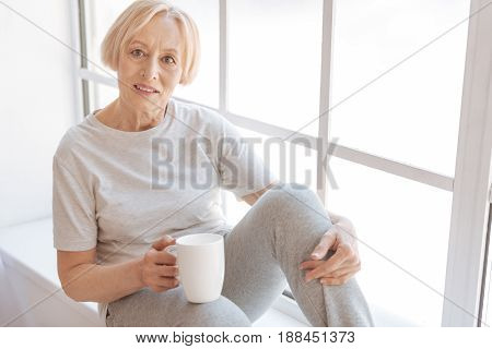 Healthy habits. Attractive woman keeping smile on her face holding cup in right hand while looking straight at camera