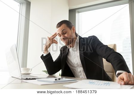 Tired of hard work businessman sitting at office desk showing finger gun aims at head. Entrepreneur has suicidal thoughts because of too much difficult job, exhausting of problems, stress and overwork