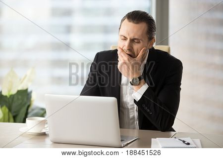 Man yawning while sitting at desk in front of laptop. Businessman struggling with drowsiness at workplace. Entrepreneur feeling severe lack of sleep, fatigue because of after-hour work. Overworking