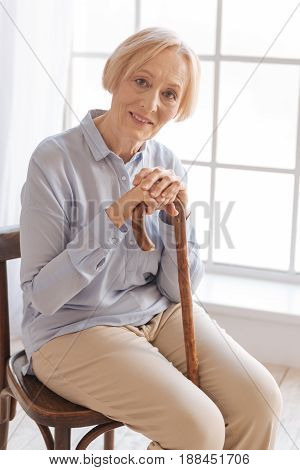 Feel yourself. Delighted elderly woman sitting on the chair bowing her head while looking straight at camera