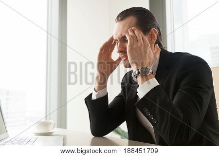 Frustrated man with closed eyes massaging temples at desk in office. Businessman suffers from migraine headache caused by high blood pressure. Tired entrepreneur feels nervous tension, stress at work