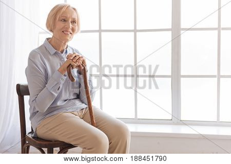 Keep your smile. Attractive woman putting hands on the cane sitting in semi position while waiting for appointment