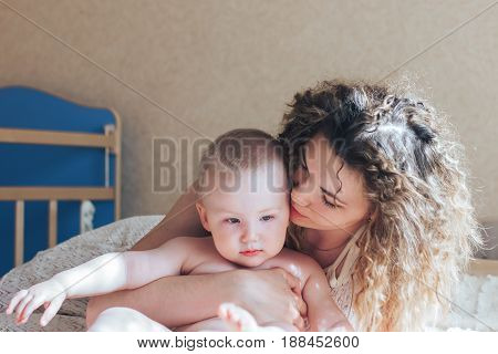 Mother Kissing Baby Son As They Lie In Bed Together