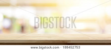 Wood table top on blur kitchen window banner background - can be used for display or montage your products (foods)