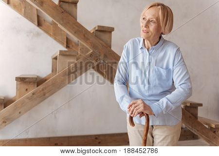 Be confident. Delighted mature woman wearing blue shirt leaning hands on the cane while looking sideways