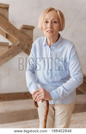 Old woman. Serious female person leaning on walking stick wrinkling her forehead and keeping mouth opened