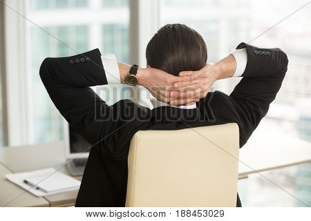 Back view of businessman sitting at desk in armchair with hands behind head. Relaxed entrepreneur thinks about future at workplace. Executive manager resting after finishing work in office. Close up