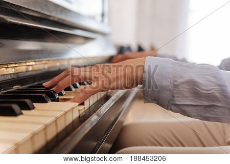 Enjoy the moment. Retired musician sitting in light room and pressing the buttons while making music