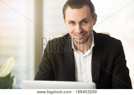 Portrait of successful businessman works on computer in office. Smiling office worker in front of laptop at workplace. Entrepreneur satisfied financial results looking in camera. Ecommerce consultant