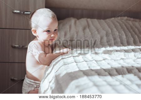 The tenderness boy stands near bed add try to go
