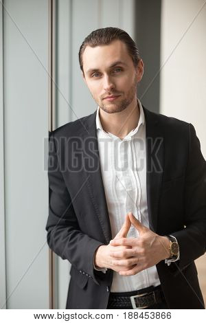 Young businessman standing near window, looking at camera. Successful entrepreneur feeling confidence in his leadership skills. Serious executive posing in office, ready to great challenges. Portrait