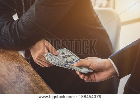 Businessmen secretly passing money - bribery and corruption concepts