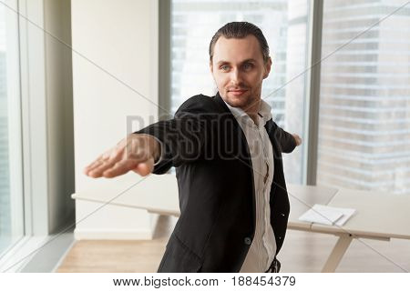 Young man wearing business suit practices yoga near work desk in modern office. Guy doing sport stretching exercises for relaxing and wellness, standing in Warrior II position, Virabhadrasana 2 pose